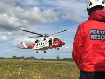 Mountain rescue medic stood in front of a helicopter